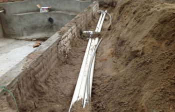 backyard swimming pool under construction- pipe system installation