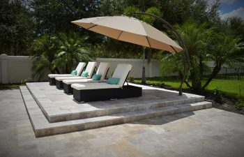 four sunbeds and umbrell on a backyard paver patio
