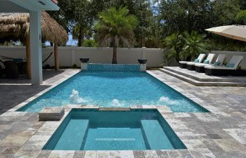 backyard swimming pool with built-in fountains and artistic pavers deck