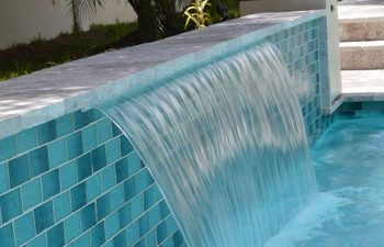 backyard pool with a waterfall