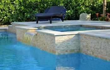 sunbed by a backyard swimming pool with water features and waterfall