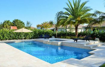 backyard swimming pool with jacuzzi and Travertine deck