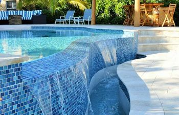 outdoor swimming pool with decorative blue tiles and waterfall