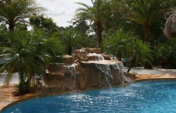 outdoor spa zone with a hardscape waterfall on the edge of the swimming pool