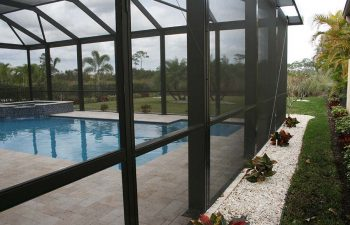 glass enclosed swimming pool with jacuzzi and paver pdeck