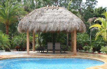 tiki hut with sunbeds on a backyard swimming pool patio