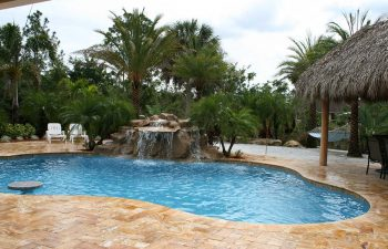 a backyard swimming pool with hardscape waterfall and tiki hut on a Travertine deck