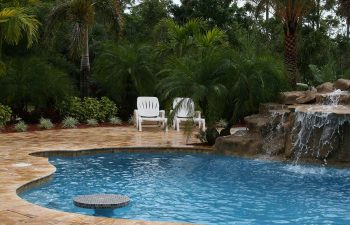 a backyard swimming pool with waterfall and tiki hut on a Travertine deck