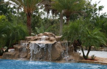 a backyard swimming pool with waterfall and hardscapes