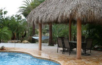 Tiki Hut and garden furniture on a deck by a backyard swimming pool