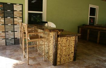 patio with tiki roof and outdoor kitchen and stools by the bar
