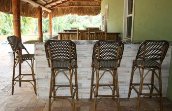 an oudoor bar with stools on a paver patio shaded by a tiki roof