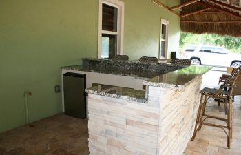 outdoor kitchen with bar and stools under tiki roof