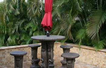 carved table with garden table umbrella and carved stools on a Travertine patio