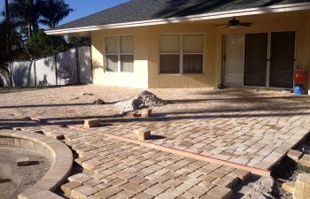 backyard swimming pool under construction - installing paver deck
