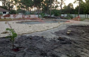 backyard swimming pool under construction - installing paver deck