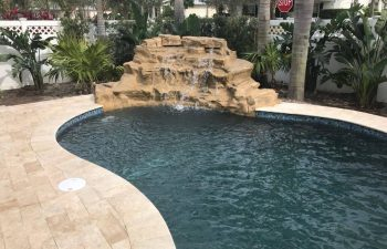 backyard swimming pool with waterfall and dark water color