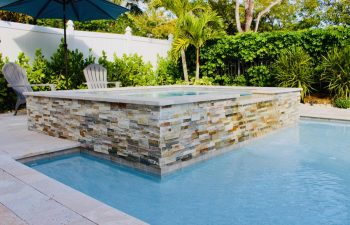backyard pool and jacuzzi with Travertine walls
