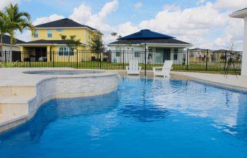 backyard swimming pool with jacuzzi and waterfall