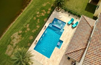aerial view of backyard swimming pool with water features and sunbeds on a deck