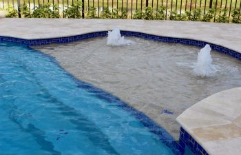 backyard swimming pool basin with two built-in fountains