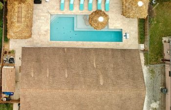 backyard aerial view of a swimming pool with sport equipment and sunbeds on a deck
