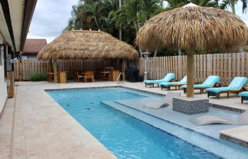backyard swimming pool with Tiki hut and sunbeds on a deck