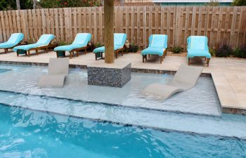 swimming pool with two sunbeds installed in water and classic sunbeds on a deck