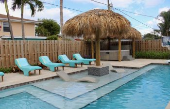 Tiki hut and sunbeds by a backyard swimming pool