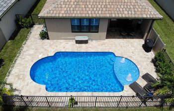 aerial view of a backyard swimming pool with two built-in fountains