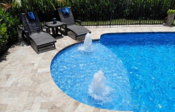 two sunbeds and a table by a backyard swimming pool with built-in fountains