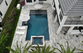 aerial view of a backyard swimming pool with jacuzzi and artistic pavers patio