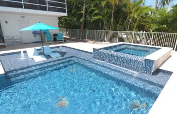modern backyard swimming pool with jacuzzi and built-in sunbeds