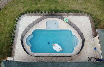 aerial view of a fenced backyard swimming pool