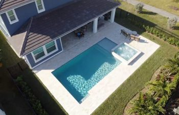 aerial view of a swimming pool with jacuzzi in a landscaped backyard