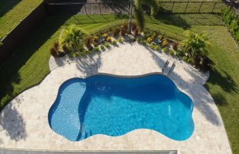 aerial view of a landscaped backyard with a swimming pool