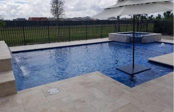 modern backyard swimming pool with jacuzzi and waterfall