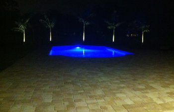 night view of a backyard swimming pool with blue light