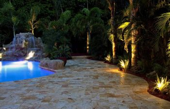 backyard swimming pool with waterfall and Travertine deck at night