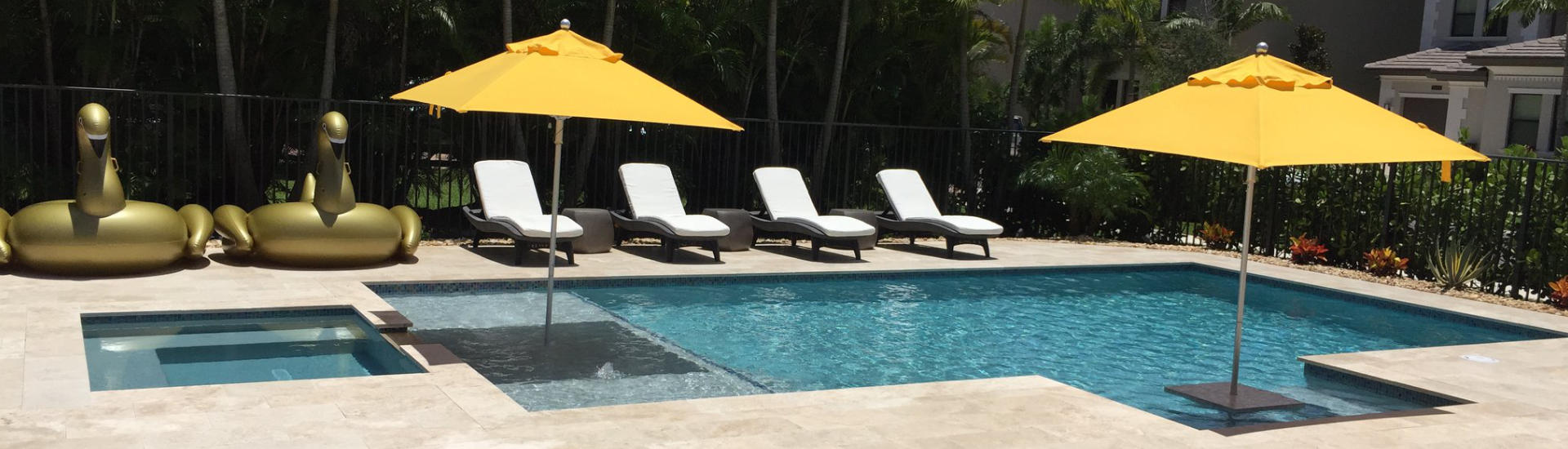 sunbeds by a backyard swimming pool with sun umbrellas insalled in water