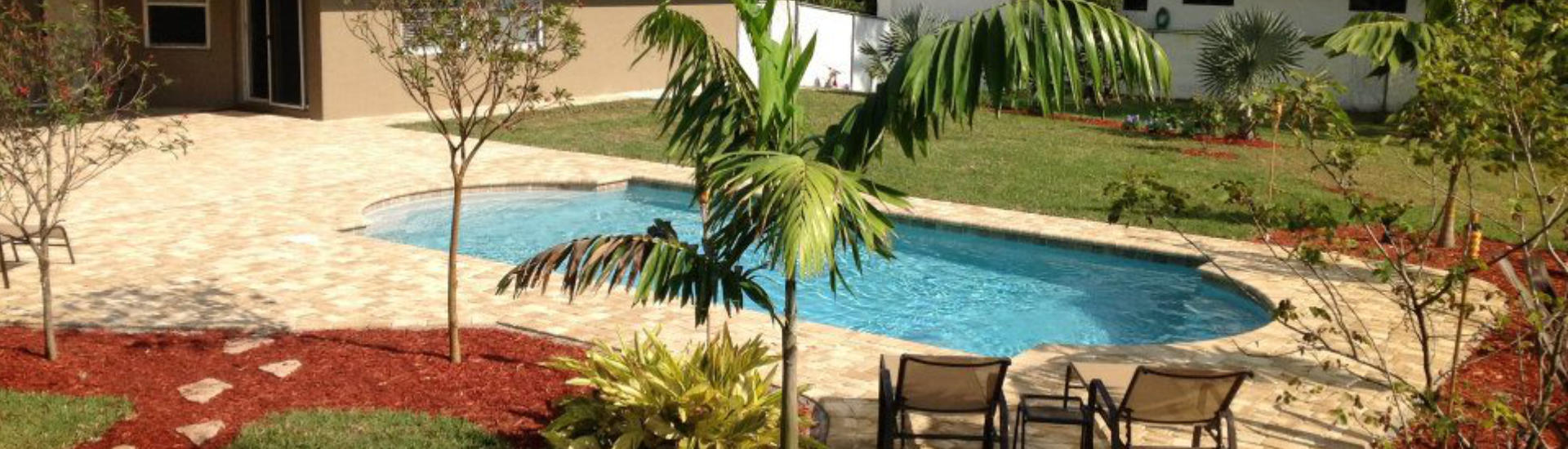landscaped backyard with a swimming pool and a Travertine paver deck