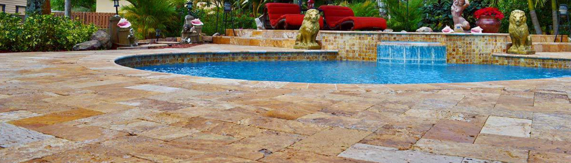 backyard swimming pool with a waterfall and two figures of lions on a deck