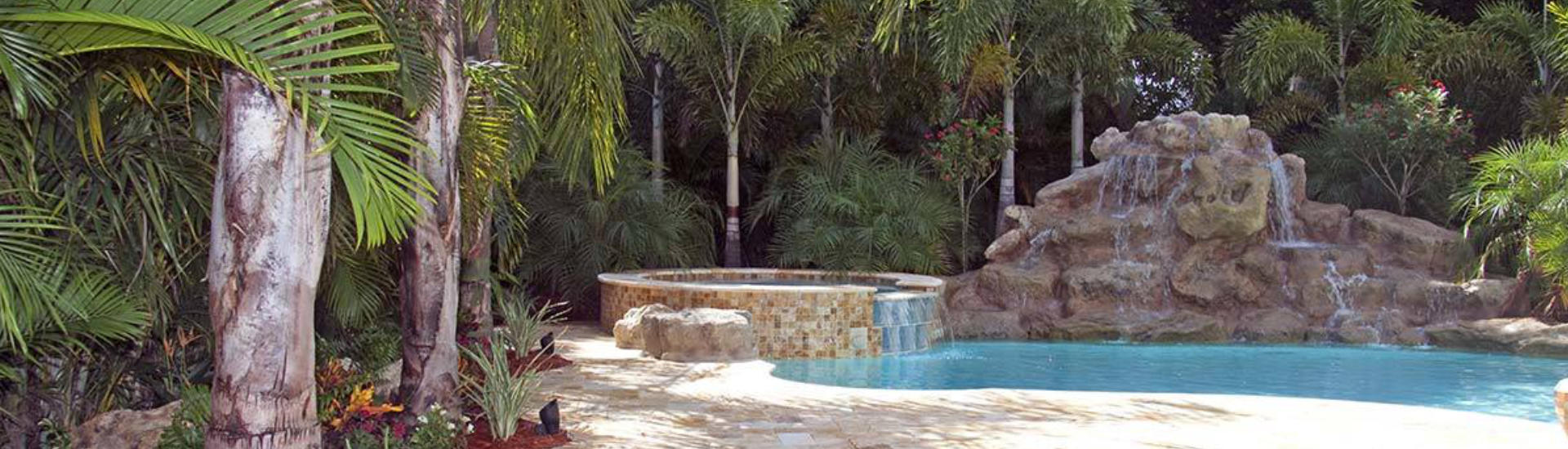 backyard swimming pool with jacuzzi and hardscape waterfall on the edge