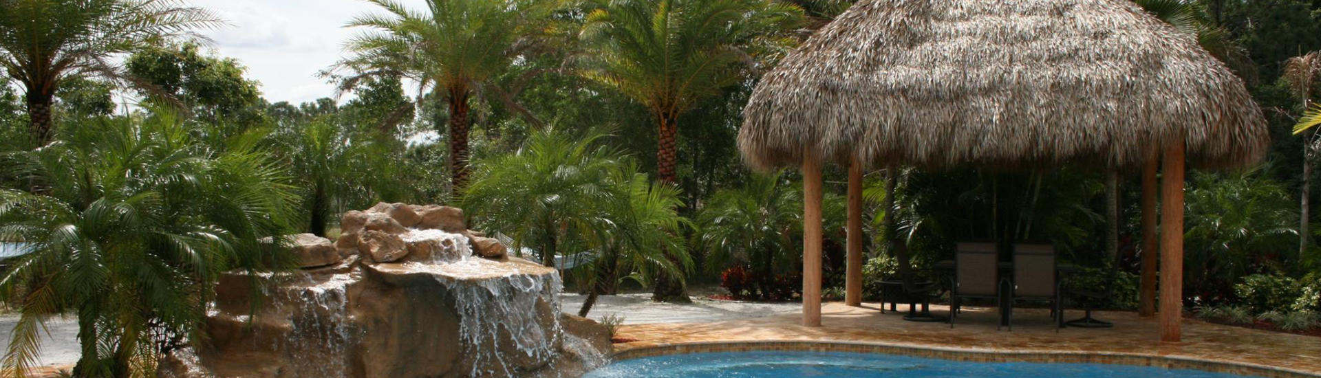 a hardscape waterfall and a tiki hut on deck of a backyard swimming pool