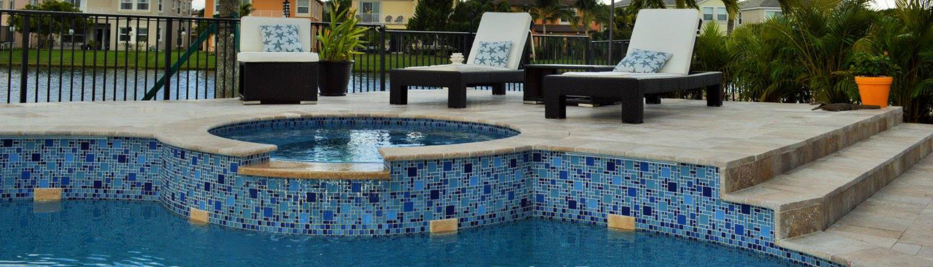backyard swimming pool with decotartive tiles and sun loungers on a deck