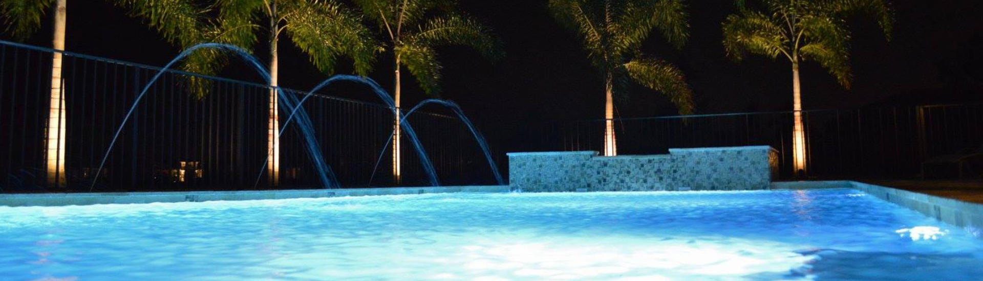 night view of a lit backyard swimming pool with fountains